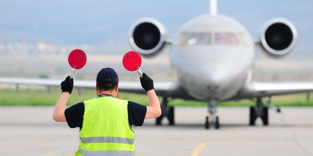 Photo pour Air traffic controller holding signs at the airport - image libre de droit