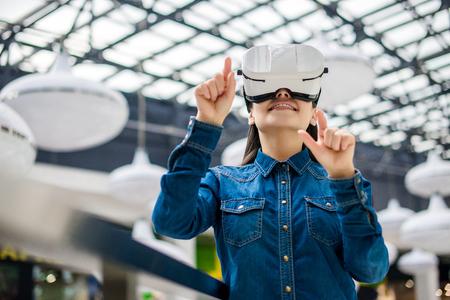 Photo pour Emotional pretty woman wearing virtual reality glasses - image libre de droit