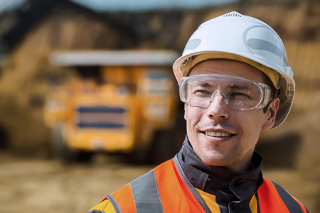 Photo pour Mine worker with huge truck on the background in open pit - image libre de droit