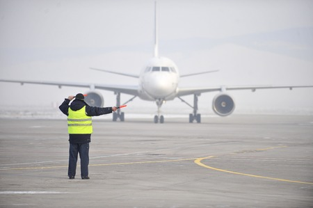 Photo pour airport worker directing an airplane as it arrived - image libre de droit