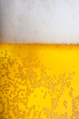 Orange beer and white froth background. Closeup view.