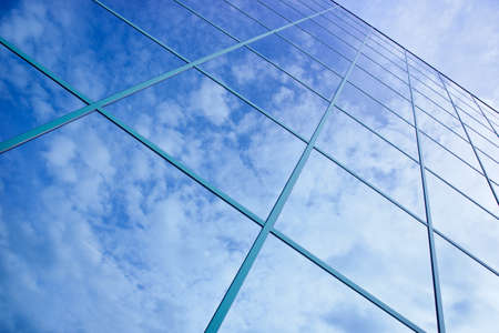 reflections of clouds and blue sky in facade of office building