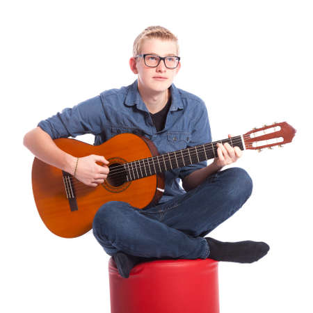 caucasian teen boy in blue wears glasses and plays the classical guitar in studio against white background