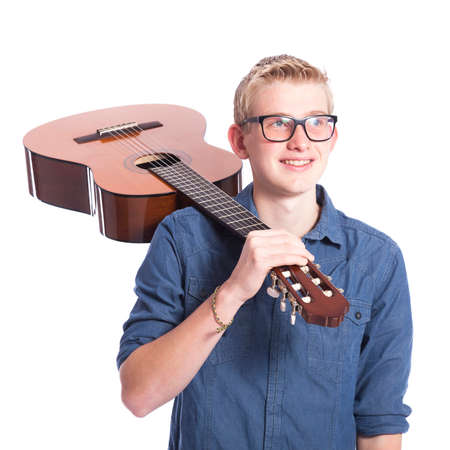 caucasian teen boy in blue wears glasses and carries classical guitar on shoulder in studio against white background