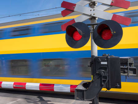 flashing red lights while blue and yellow train passes railway crossing