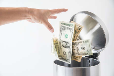 Photo for throwing away dollar in trashcan - Royalty Free Image
