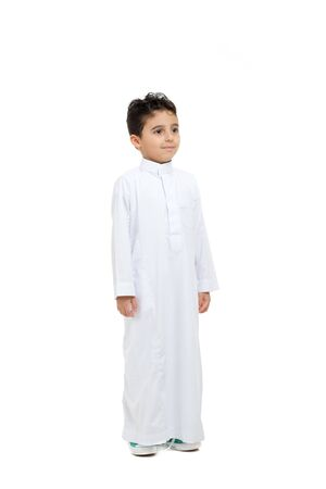 Photo pour Arab boy looking at far, wearing white traditional Saudi Thobe and sneakers, raising his hands on white isolated background - image libre de droit
