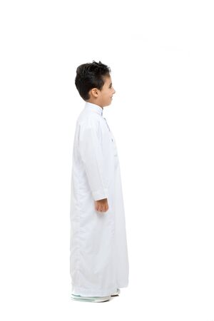 Photo pour Arab boy standing sideways, wearing white traditional Saudi Thobe and sneakers, raising his hands on white isolated background - image libre de droit