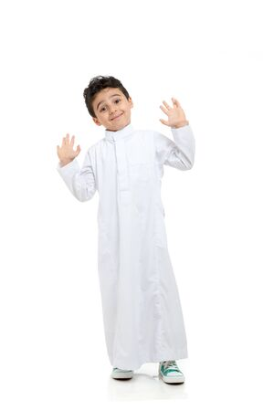 Photo pour Arab boy smiling, wearing white traditional Saudi Thobe and sneakers, raising his hands on white isolated background - image libre de droit