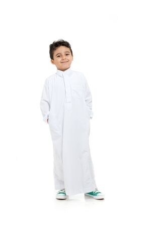 Photo pour Arab boy relaxed and smiling, wearing white traditional Saudi Thobe and sneakers, raising his hands on white isolated background - image libre de droit