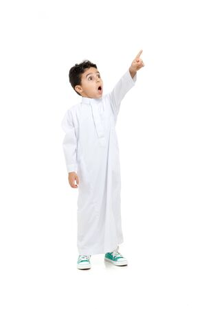 Photo pour Arab boy looking at far and pointing his finger with a big surprise on his face, wearing white traditional Saudi Thobe and sneakers, raising his hands on white isolated background - image libre de droit