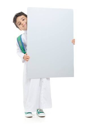 Photo pour Arab school boy raising a big white board with both hands, wearing white traditional Saudi Thobe and sneakers, raising his hands on white isolated background - image libre de droit