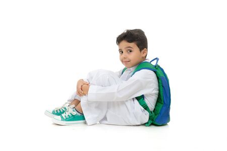 Photo pour Arab school boy sitting on ground with a smile on his face, wearing white traditional Saudi Thobe, back pack and sneakers, raising his hands on white isolated background - image libre de droit