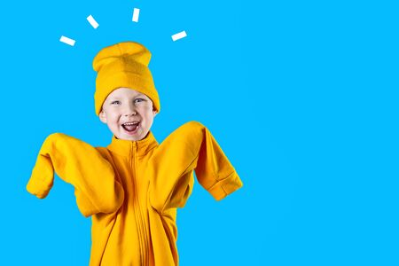 Foto de A cheerful guy in a bright yellow jacket and hat enthusiastically rejoices on a blue background - Imagen libre de derechos
