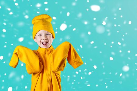 Foto de A cheerful guy in a bright yellow jacket and hat enthusiastically rejoices on a mint background - Imagen libre de derechos