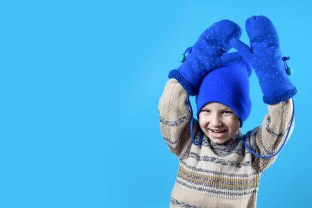 Foto de happy boy in a blue hat, mittens and sweater on a bright colored background - Imagen libre de derechos