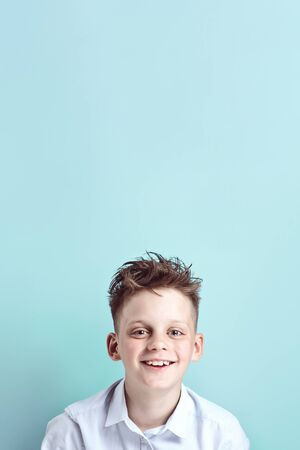 Foto de cheerful boy stands and smiles in a light shirt on a bright colored background - Imagen libre de derechos