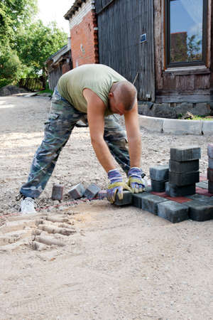 A road worker installed paving stones on a new road