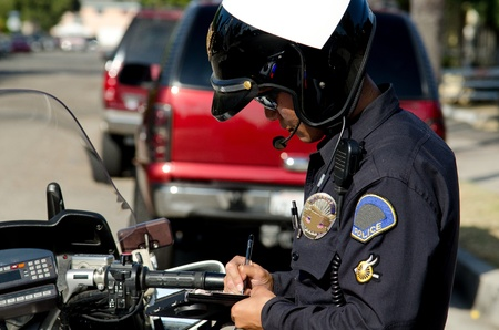 a motorcycle police officer writing a ticket to a speeding driver.