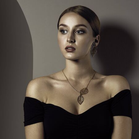 Photo pour Portrait of pretty red head girl wearing necklace and earrings - image libre de droit