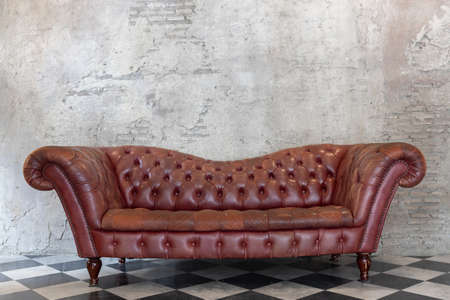 Photo pour front view of luxury red genuine leather sofa on checkered pattern marble tiles floor with brick cement wall - image libre de droit