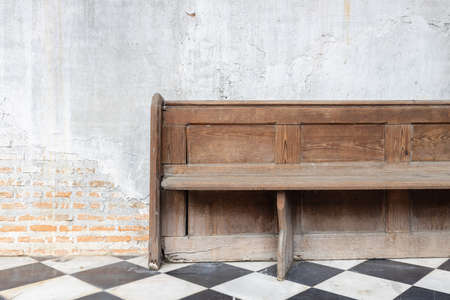 Photo pour front view of old wooden bench on checkered pattern marble tiles floor with brick and cement wall background in church - image libre de droit