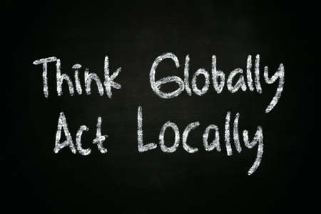 The words Think Globally Act Locally written with chalk on blackboard