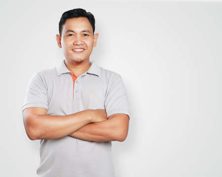 Photo for Photo image portrait of a cute handsome young Asian man smiling confidently with his arms crossed in front of his chest - Royalty Free Image
