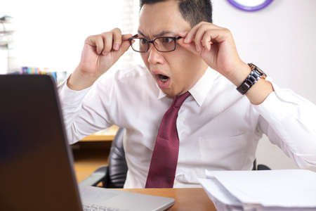 Foto de Portrait of Asian businessman looking at his laptop with shocked stunned worried facial expression gesture, man at office - Imagen libre de derechos