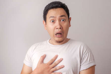 Foto de Portrait of young funny Asian man shocked or surprised expression with mouth open, worried to see something bad happen - Imagen libre de derechos