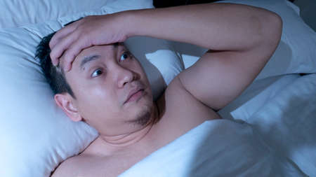 Portrait of Asian man waked up in the midnight for having nightmare, shocked panic gesture on the bed
