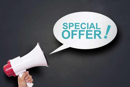 Photo pour Hand holding megaphone agains blackboard with big sale special offer, announcement marketing concept - image libre de droit