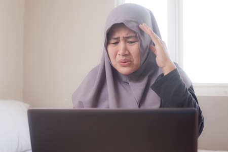 Photo pour Sad muslim businesswoman crying expression to see bad financial report on laptop, loss in stock market concept - image libre de droit