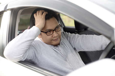 Photo pour Portrait of funny Asian male driver get bored in his car trapped in traffic jam, tired lazy facial expression gesture - image libre de droit