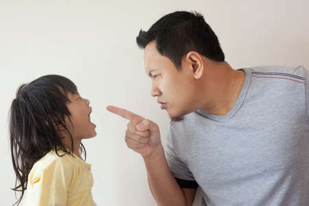 Foto de Young Asian father and little baby girl daughter arguing, screaming each other, dad mad at his kid - Imagen libre de derechos