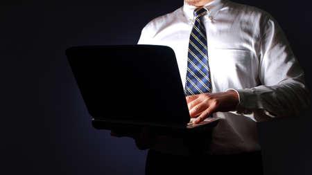 Foto de Businessman typing on laptop in the dark, executive manager working secretly concept - Imagen libre de derechos