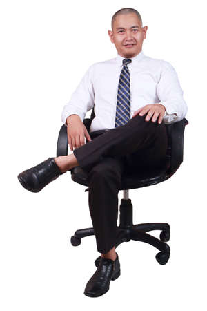 Photo pour Happy succesful young Asian businessman smiling while sitting on chair, isolated on white - image libre de droit