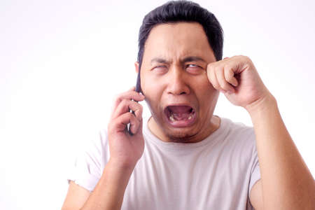 Photo pour Young Asian man crying shocked worried expression by the phone. Over white background - image libre de droit