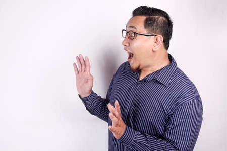 Foto de Portrait of young Asian man shocked to see something on his side, excited gesture with copy space - Imagen libre de derechos