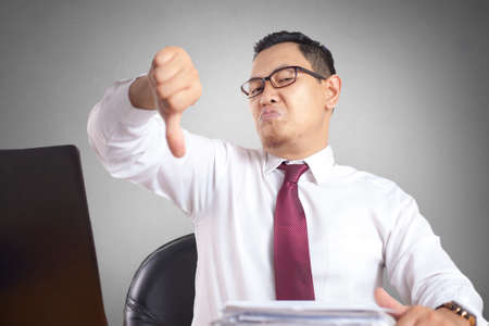 Photo for Angry Asian boss manager businessman shows thumb down gesture, upset disappointed gesture - Royalty Free Image