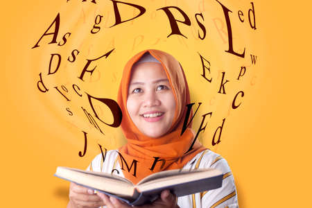 Foto de Portrait of beaautiful young Asian muslim woman smiling when reading book, magical book with letters flying from it - Imagen libre de derechos