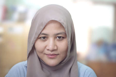 Photo pour Portrait of beautiful muslim woman wearing hijab smiling over blurred background - image libre de droit