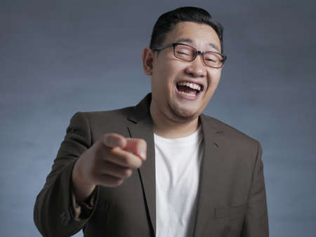 Photo for Asian businessman wearing suit laughing expression, pinting forward to camera. Close up body portrait - Royalty Free Image