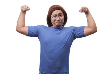 Photo for Portrait of funny narcissictic Asian man smiling proudly while showing double biceps pose, strength over confidence concept - Royalty Free Image