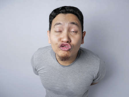 Foto de Portrait of funny silly Asian man trying to kiss, against grey background - Imagen libre de derechos
