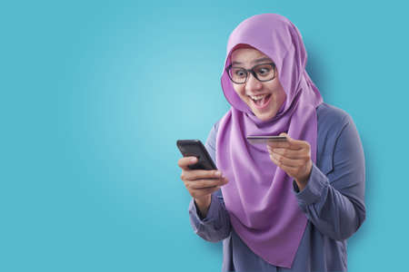 Photo for Portrait of Asian muslim woman smiling and making purchase buying online from her mobile phone, e-commerce concept - Royalty Free Image