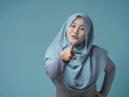 Foto de Portrait of cute beautiful Asian muslim lady smiling to camera and pointing forward as if choosing you concept - Imagen libre de derechos
