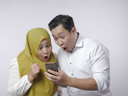 Photo pour Portrait of Asian muslim couple shocked or surprised to see something on smart phone, big eyes and opened mouth expression - image libre de droit