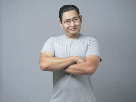 Photo pour Photo image portrait of funny young attractive cute Asian man smiling happily, with arms crossed - image libre de droit