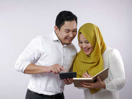 Photo for Portrait of Asian young muslim couple checking analyzing their family financial management report, young family housband and wife happy to see their financial plan - Royalty Free Image